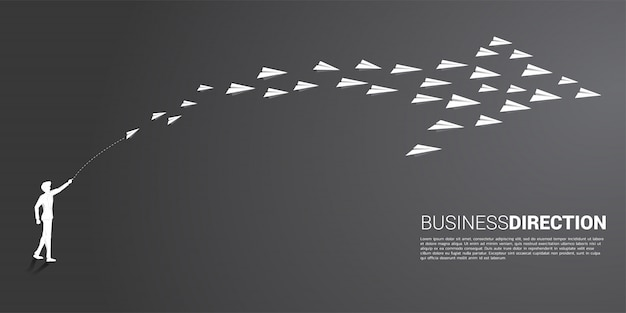 Silhouette of businessman throw out white origami paper airplane is arranged in a shape of big arrow