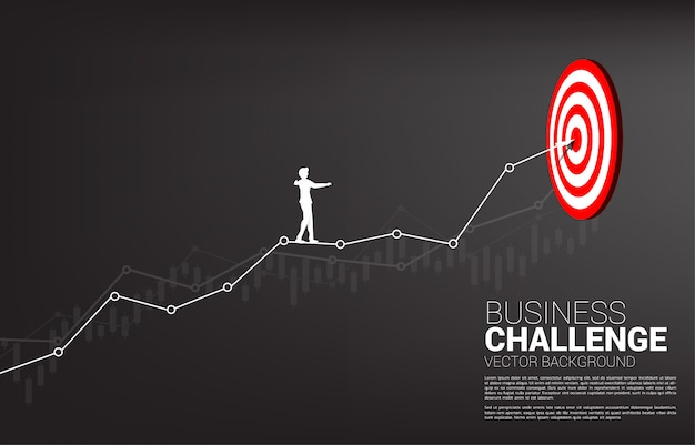 Silhouette of businessman walk rope on line graph to center of dartboard. concept of targeting and business challenge.route to success.