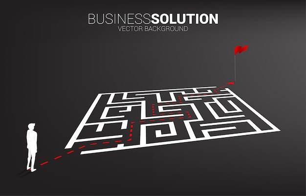 Silhouette of businessman with route path to exit the maze to flag
