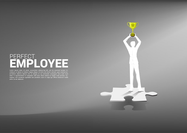 Silhouette of businessman with trophy standing on jigsaw piece.