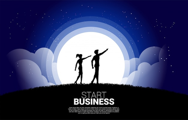 Silhouette of businesswoman and business man point forward ahead at night. concept of vision mission and entrepreneur