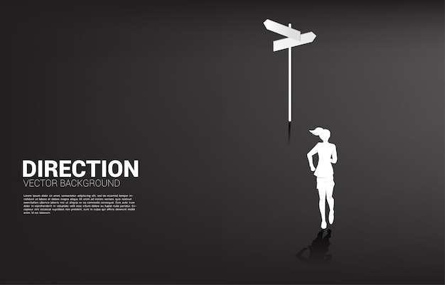 Silhouette of businesswoman standing at direction signage. concept of time to make decision in business direction