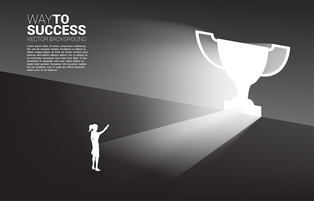 Silhouette businesswoman standing in light from exit door shape trophy. business concept of route to winner and champion