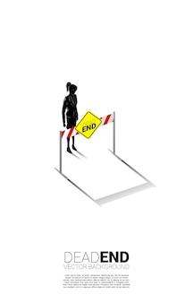 막다른 간판과 함께 서 있는 실루엣 사업가. 비즈니스 또는 경력 경로의 끝에서 잘못된 결정의 개념.