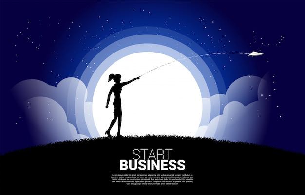 Silhouette of businesswoman throw out origami paper airplane at night.