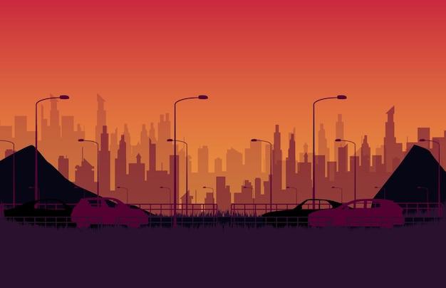 オレンジ色のグラデーションで街の夜と道路上のシルエット車