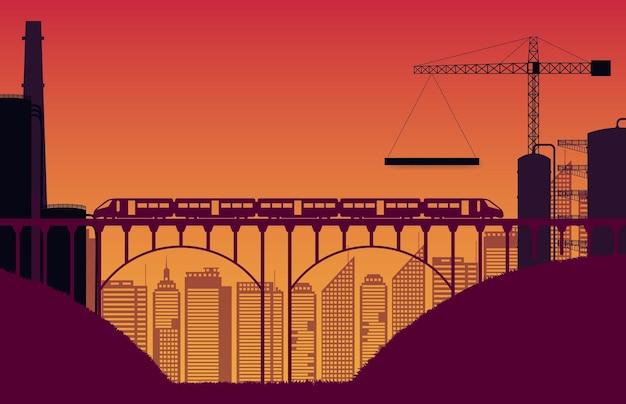 オレンジ色のグラデーションで橋とシルエットの建設現場と列車