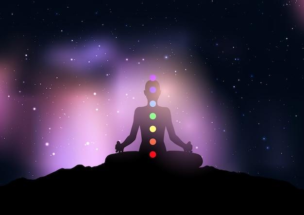 Siluetta di una donna con chakra nella posa di yoga contro il cielo notturno stellato
