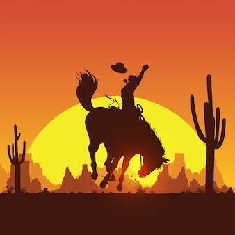 日没で野生の馬に乗るカウボーイのシルエット