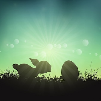 Silhouette of an Easter bunny and egg in grassy landscape