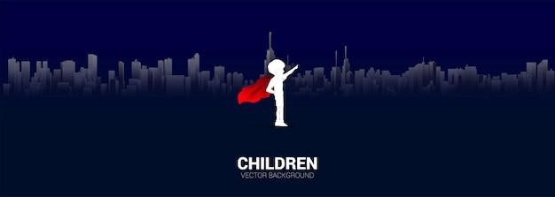 슈퍼 히어로 슈트를 입은 소년의 실루엣은 도시의 하늘을 가리킵니다. 아이들의 교육 시작과 미래의 개념.