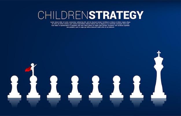 전당포에서 왕까지 체스 조각에 서 있는 슈퍼히어로 정장을 입은 소년의 실루엣. 아이들의 교육 시작과 미래의 개념.