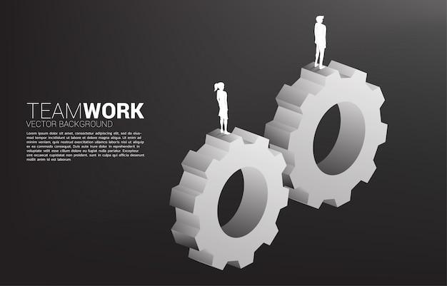 ビジネスマンと一緒に動作する歯車の上に立っている実業家のシルエット。ビジネスチームワークの概念。