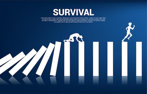 도미노 붕괴에 사업가 크롤링의 실루엣입니다. 비즈니스 산업의 개념이 중단됩니다.
