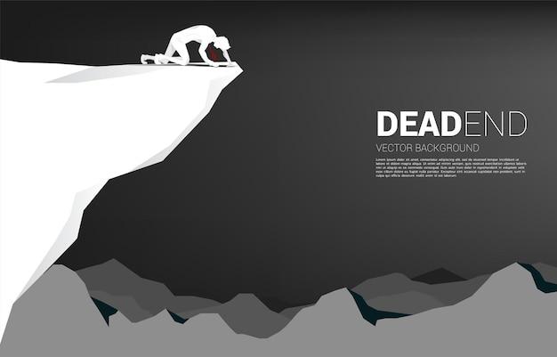 절벽에 크롤 링 하는 사업가의 실루엣입니다. 죽은 사업과 장애물에 대한 개념.