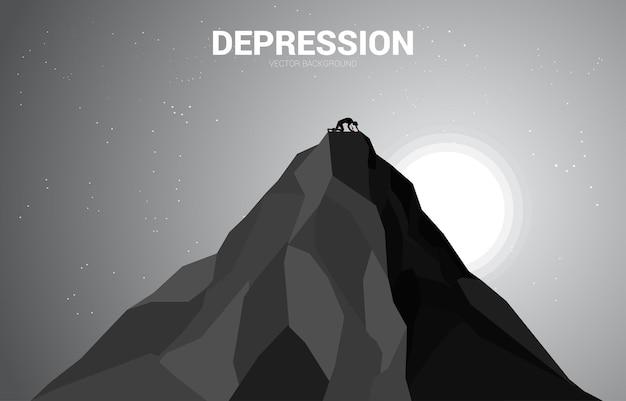 산 꼭대기에 크롤 링 하는 사업가의 실루엣입니다. 성공 비즈니스의 우울증에 대한 개념입니다.