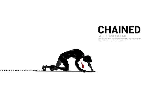 다리에 사슬로 기어가는 사업가의 실루엣입니다. 우울증과 장애물 사업에 대한 개념입니다.