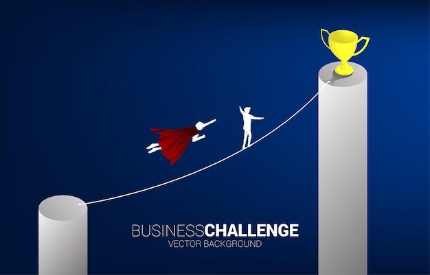비행하는 사업가의 실루엣은 밧줄을 타고 트로피를 향해 걸어가는 남자와 경쟁합니다. 비즈니스 위험 및 경력 경로에 대한 개념