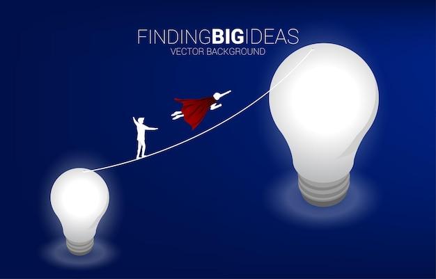Силуэт летящего бизнесмена соревнуется с человеком, идущим по веревочной прогулке от маленькой лампочки до большой. концепция бизнес-риска и карьерного роста