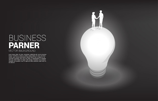Силуэт верхней части рукопожатия бизнесмена верхней части электрической лампочки. концепция совместной работы партнерства и сотрудничества.