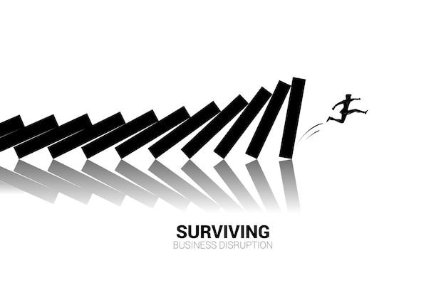 ビジネスマンのシルエットはドミノ崩壊から飛び降ります。ビジネス業界の混乱の概念