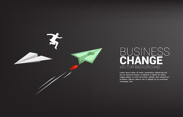 ビジネスマンのシルエットは、白い折り紙紙飛行機から方向転換のための紙幣お金にジャンプします。ビジネスの方向性を変えるビジネスコンセプト。企業ビジョンの使命。