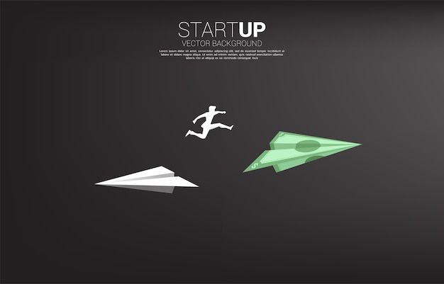ビジネスマンのシルエットは、白い折り紙の紙飛行機から方向を変えるために紙幣のお金にジャンプします。ビジネスの方向性を変えるというビジネスコンセプト。企業ビジョンの使命。