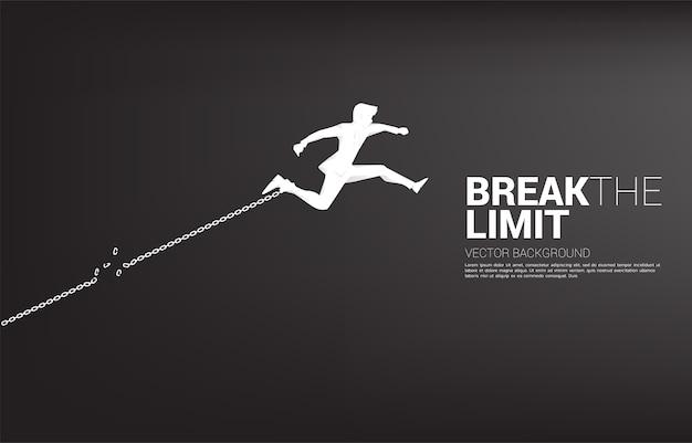 Силуэт бизнесмена прыгает, чтобы сломать цепь у ног