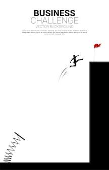 사업가의 실루엣 발판과 절벽에 붉은 깃발을 점프. 사업 부스트와 성장의 개념.