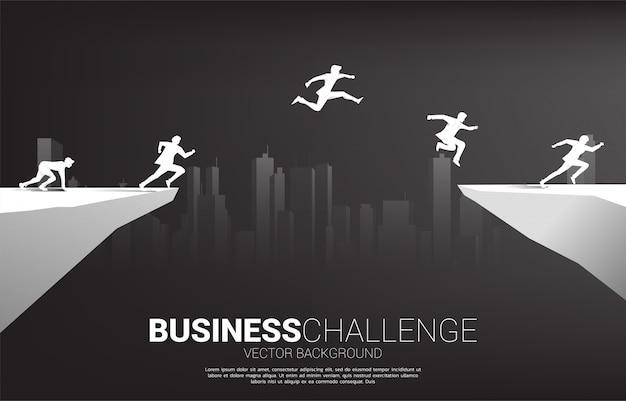 都市の背景を持つ谷のギャップを飛び越えて実業家のシルエット。ビジネスチャレンジリスクの概念。