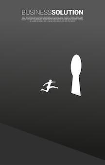 壁の鍵穴出口にジャンプするビジネスマンのシルエット。ソリューションコンセプトのビジョンミッションとビジネスの目標を見つける