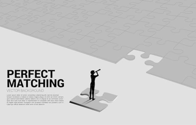 퍼즐 조각에 망원경을 통해 찾고 사업가의 실루엣. 임무를 위한 비즈니스 개념과 새로운 목표를 찾는 것.