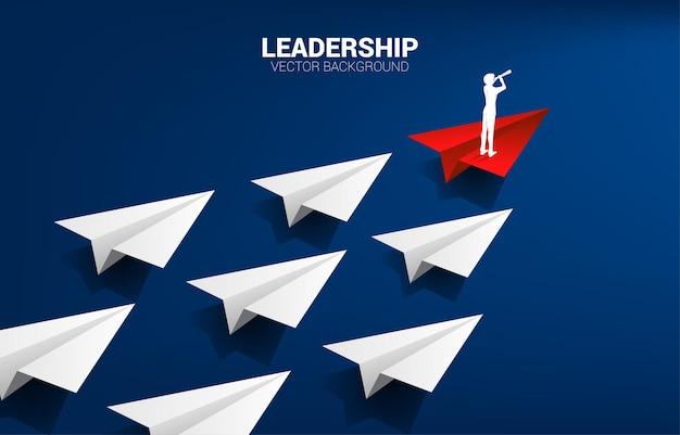 흰색의 그룹을 이끄는 빨간색 종이 접기 종이 비행기에 망원경을 통해 보는 사업가의 실루엣. 리더십과 비전 임무의 비즈니스 개념입니다.