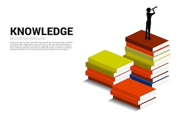 Силуэт бизнесмена, смотрящего через телескоп, стоящий на вершине стопки книг. предпосылка концепции силы знания.