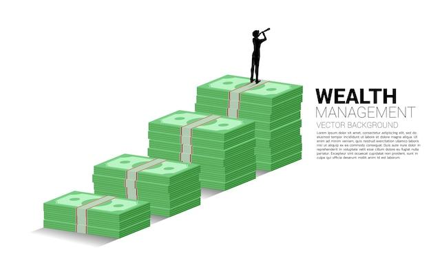 지폐 더미와 함께 성장 그래프 위에 서 있는 망원경을 통해 보고 있는 사업가의 실루엣. 성공 투자 및 비즈니스 성장의 개념