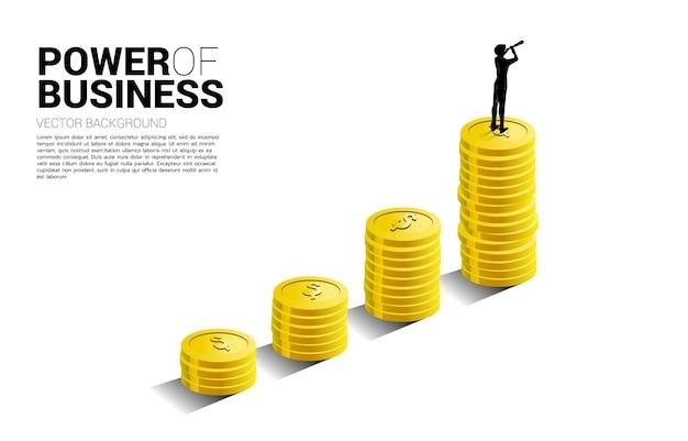 동전 더미와 함께 성장 그래프 위에 서 있는 망원경을 통해 보고 있는 사업가의 실루엣. 성공 투자 및 비즈니스 성장의 개념입니다.