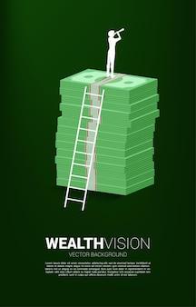 사다리가 있는 지폐 더미 위에 서 있는 망원경을 통해 보는 사업가의 실루엣입니다. 성공 투자 및 비즈니스 성장의 개념