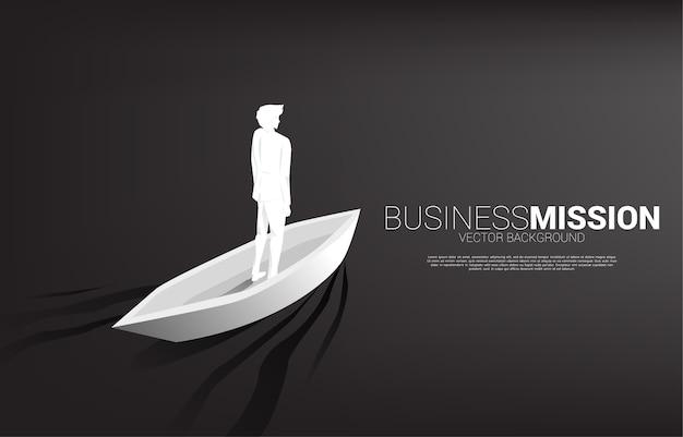 前進するボートに乗っているビジネスマンのシルエット。リーダーシップとビジョンミッションのビジネスコンセプト。