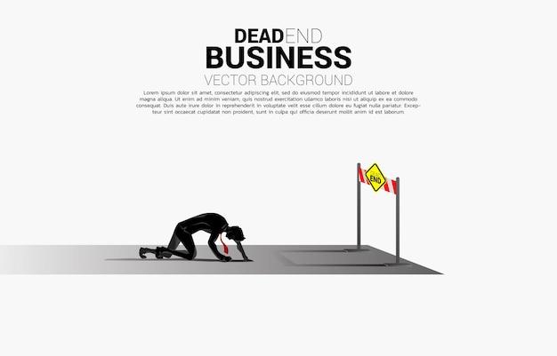 막다른 표지판이 있는 도로 끝에 무릎을 꿇고 있는 사업가의 실루엣입니다. 우울증과 장애물 사업에 대한 개념입니다.