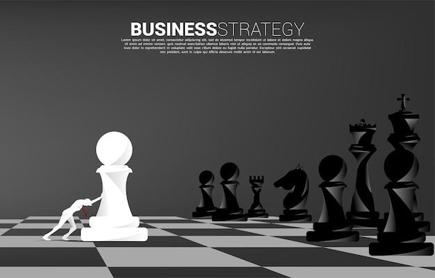 ビジネスマンのシルエットは、ポーンのチェスの駒をチェス盤に押し込みます。事業戦略とマーケティング計画の概念