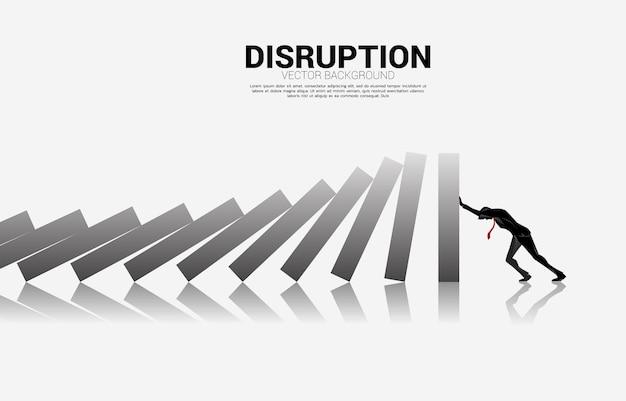 ドミノの落下を止めるために押すビジネスマンのシルエット。ドミノ効果を止めようとするビジネスコンセプト