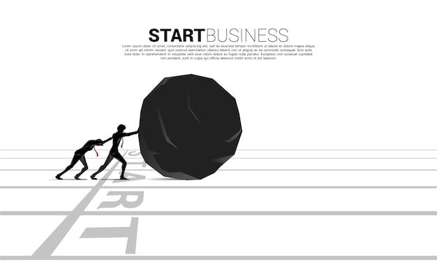 출발선에서 바위를 밀고 있는 사업가의 실루엣. 비즈니스 도전의 개념과 열심히 일하십시오.