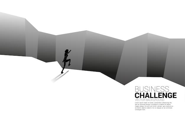 深淵への一歩を踏み出すビジネスマンのシルエット。ビジネスチャレンジと勇気の男の概念