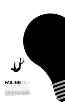 Силуэт бизнесмена поскользнулся и падал от лампочки. концепция неудачной идеи и бизнеса.