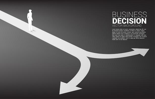 岐路に立っているビジネスマンのシルエット。ビジネスの方向性を決定する時間の概念
