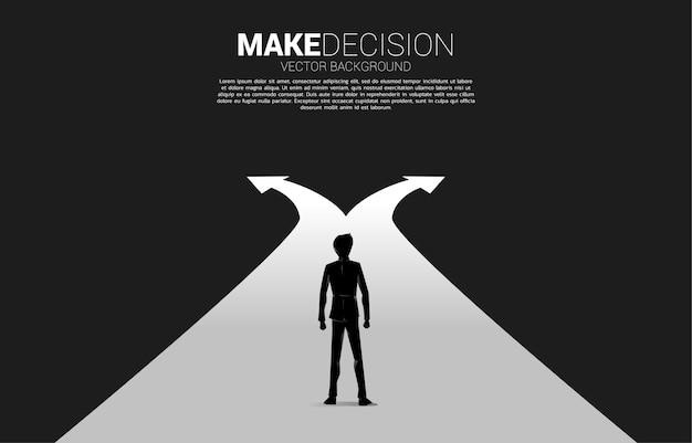 交差点に立っているビジネスマンのシルエット。ビジネスの方向性を決定する時間の概念