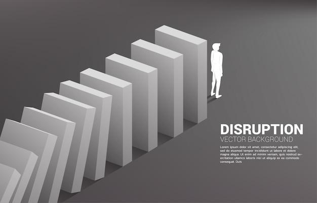도미노 붕괴의 끝에 서있는 사업가의 실루엣. 비즈니스 산업 중단의 개념