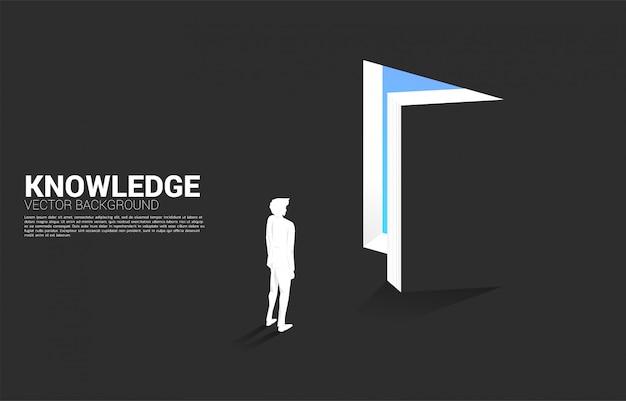 開かれた本からの光の中で立っている実業家のシルエット。本の知識の概念