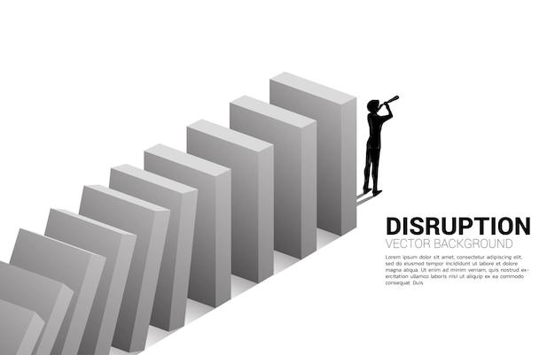 도미노 붕괴의 끝에 망원경을 통해 보고 서 있는 사업가의 실루엣. 비즈니스 산업 혼란의 개념