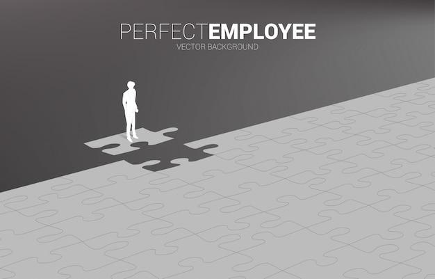 最後のジグソーピースに立っているビジネスマンのシルエット。完全採用のコンセプト。人事。適任者を適任者に任せなさい。